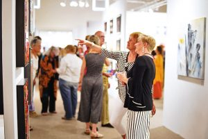 Attendees & Collectors admire this year's array of new artwork